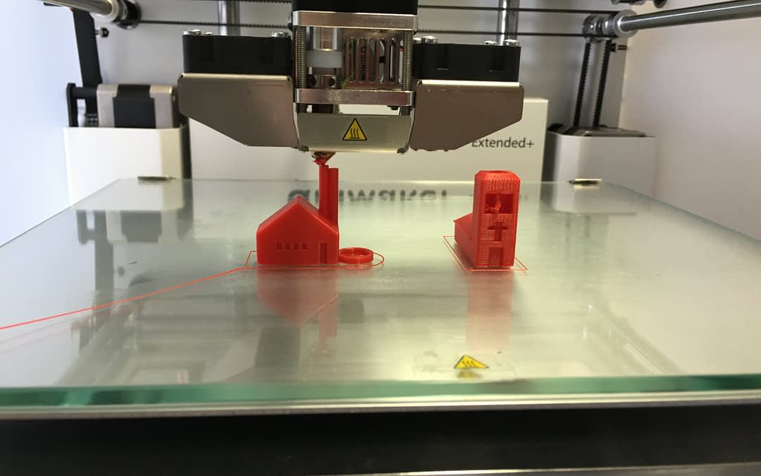 A 3D Printer printing out miniature D&D figurines